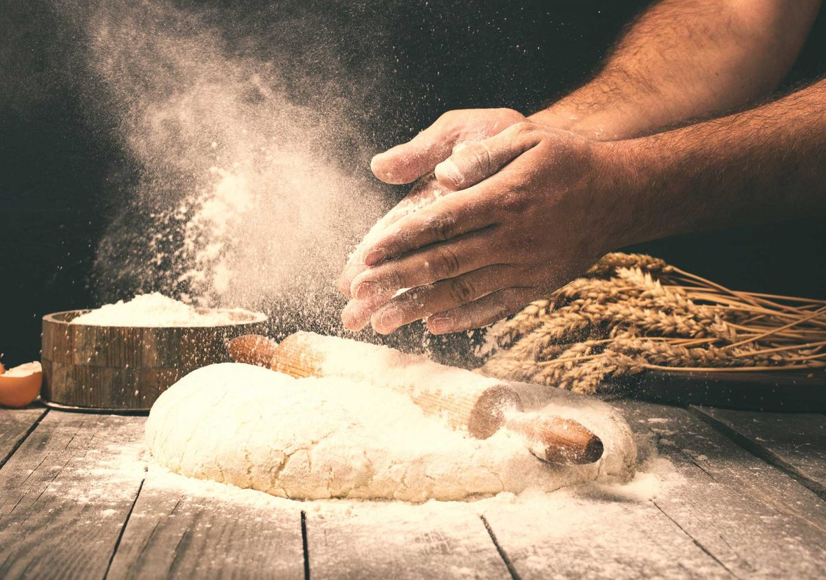 Man rolling dough into bread